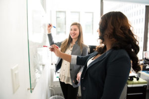 two women working at whiteboard