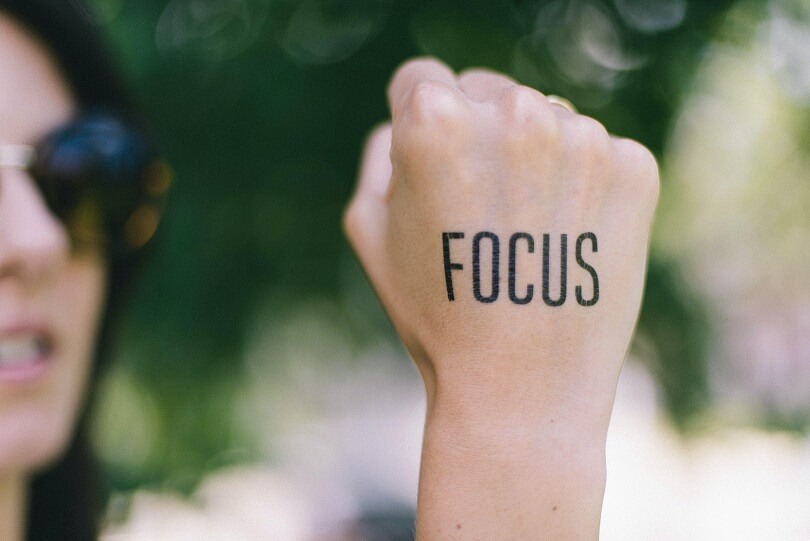 clarify my calling with focus - a woman with word focus written on hand