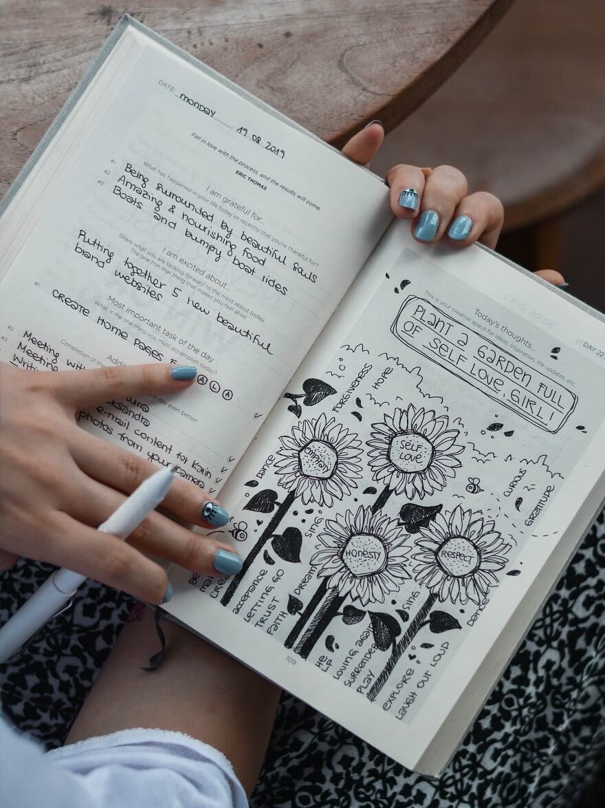 Woman writing positive thoughts into a journal